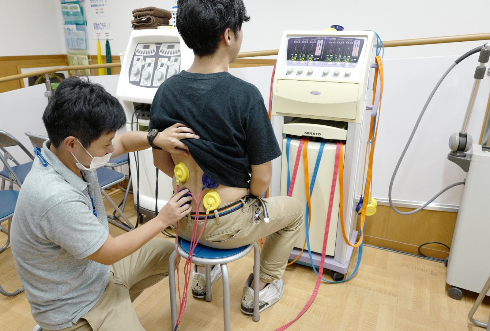 干渉電流型低周波治療器を用いて治療中